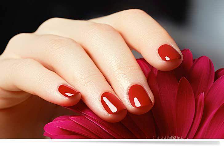 Rote Gelnägel und eine schöne Hand einer Frau