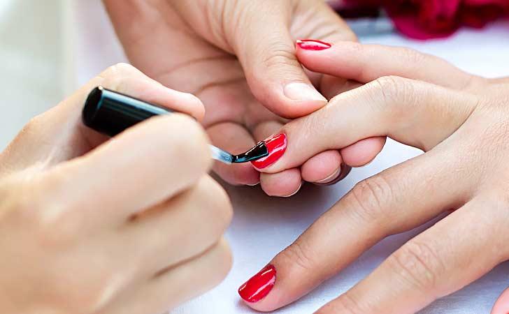 Gutes Nageldesign auf roten Fingernägel praktiziert von einer Kosmetikerin