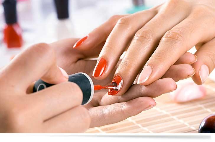 Helles Nagelstudio und rote Fingerngel die gerade professionell lackiert werden