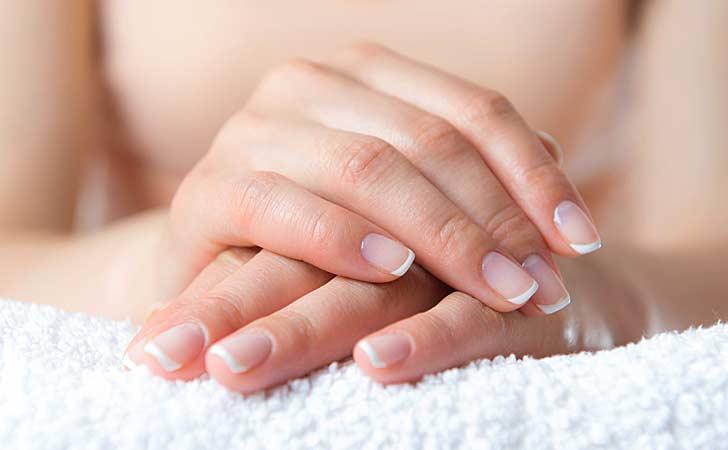 Gepflegtes Nagelstudio und eine Frau die ihre frischen Fingernägel nach einer Maniküre zeigt