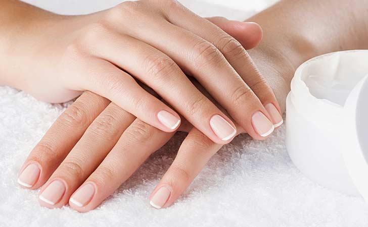 Sanfte Hände mit schönen Fingernägel neben einer Tube mit Creme