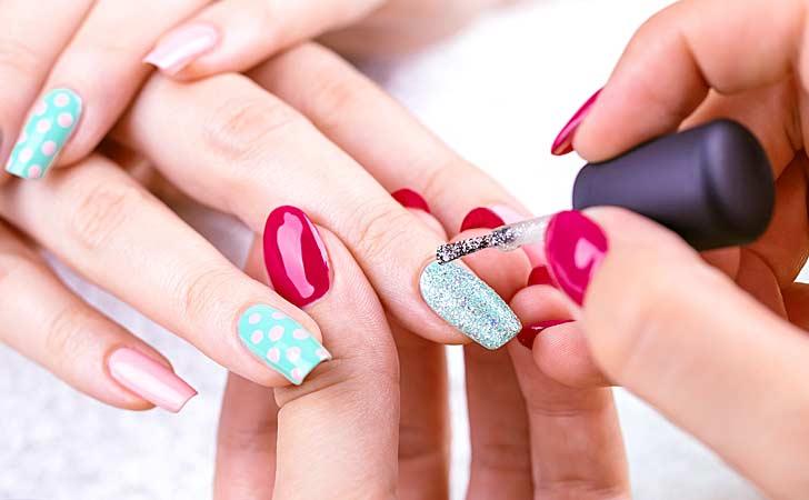 Eine Kosmetikerin praktiziert kreatives Nailart an der Hand einer Kundin