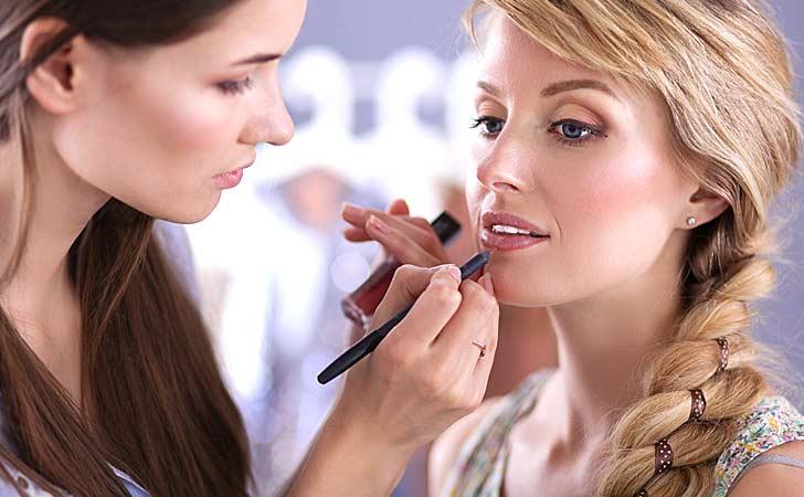 Junge Kosmetikerin macht das Make-Up bei einer hübschen Frau