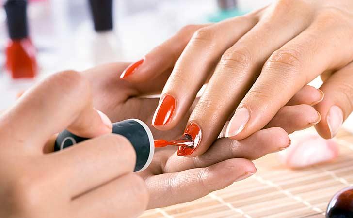 Helles Nagelstudio in dem gerade Fingernägel rot lackiert werden