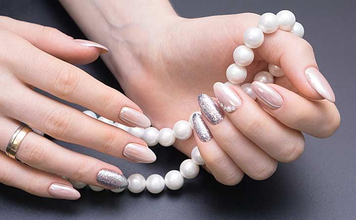 Schöne Fingernägel mit spitzer Nagelform und einer edlen Perlenkette auf einem Tisch